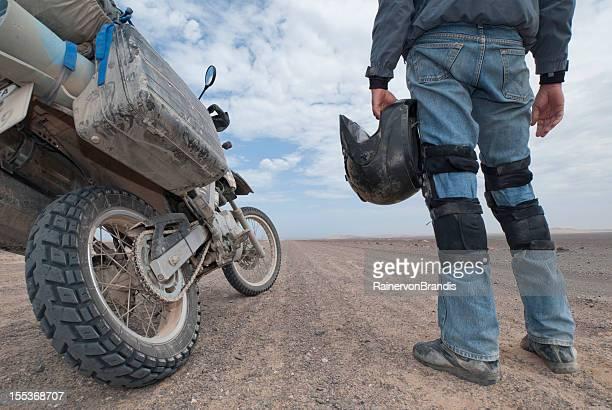 adventure motorcycle rider stands next to bike