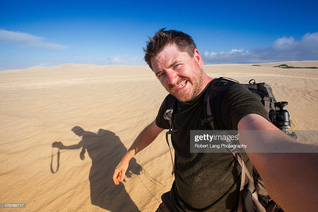 Adventure photographer self portrait in sand dunes