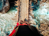 First person view of hiker walking over a bridge while trekking in Annapurna Range on Himalayas, Nepal