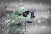 Wintry scene of man in coat battling against a winter blizzard.