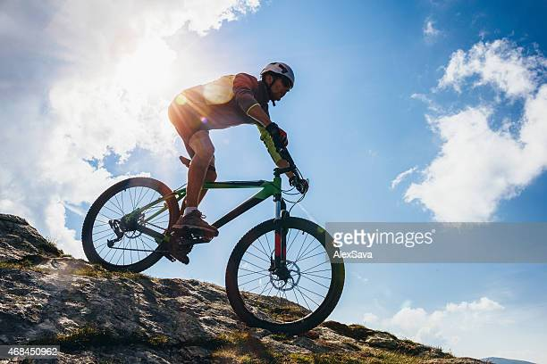 Adventurous Man riding his bike on steep terrain