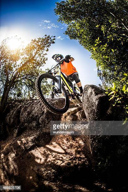 Adventurous mountain biker going over rocks on an off-road trail