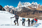 Adventurous People of variety of Age Origin and Ethnicity making Climb in high Altitude Mountains walking on Glacier with heavy Snow using trekking Poles and other Gear