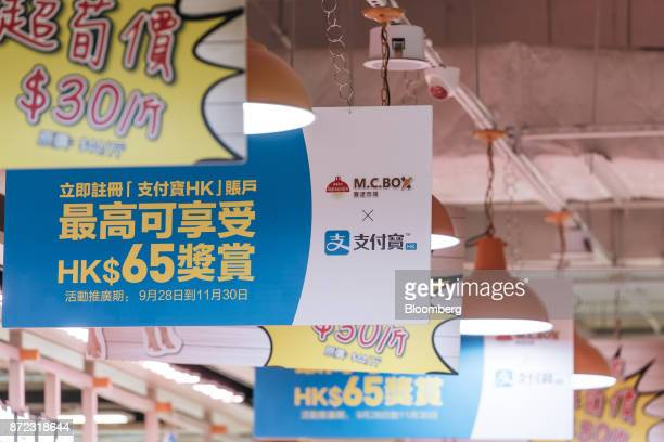 Advertisement banners for Ant Financial Services Group's Alipay an affiliate of Alibaba Group Holding Ltd second left and second right hang inside MC...