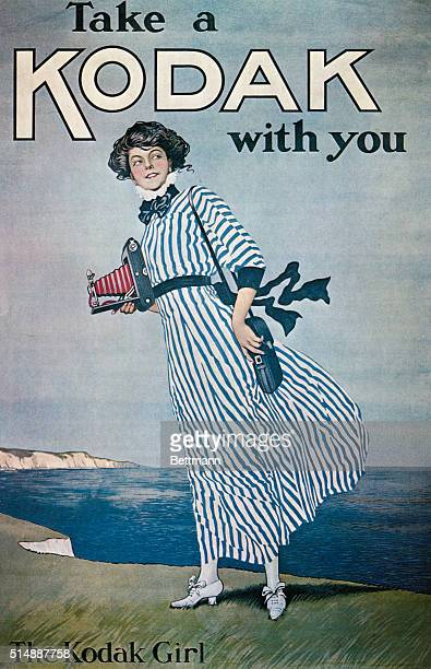 Advertisement for Kodak cameras featuring 'The Kodak Girl' well dressed and standing on a windswept cliff with camera in hand