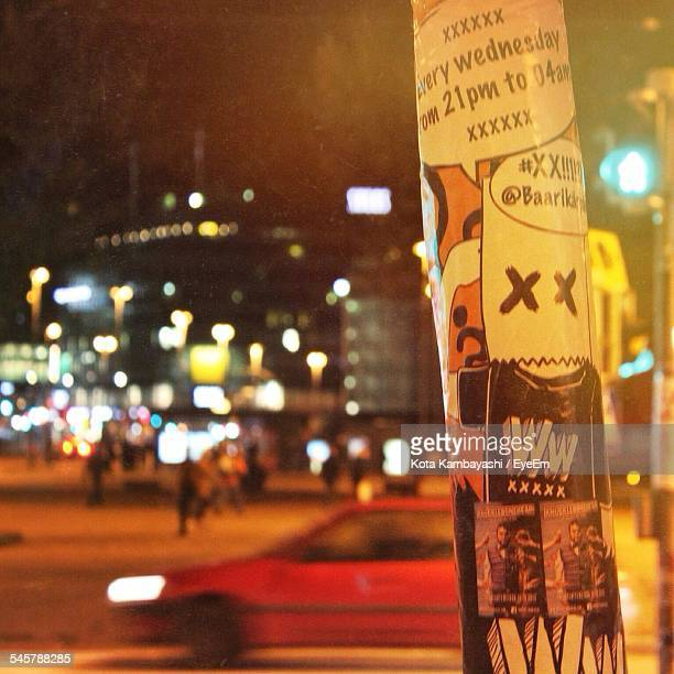 Advertisement On Pole At City Street During Night