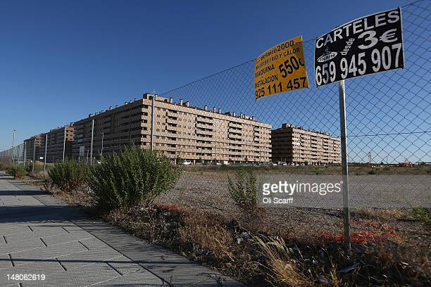 Advertisements are attached to a chainlink fence in front of a largescale residential development which stands predominantly unoccupied on July 6...