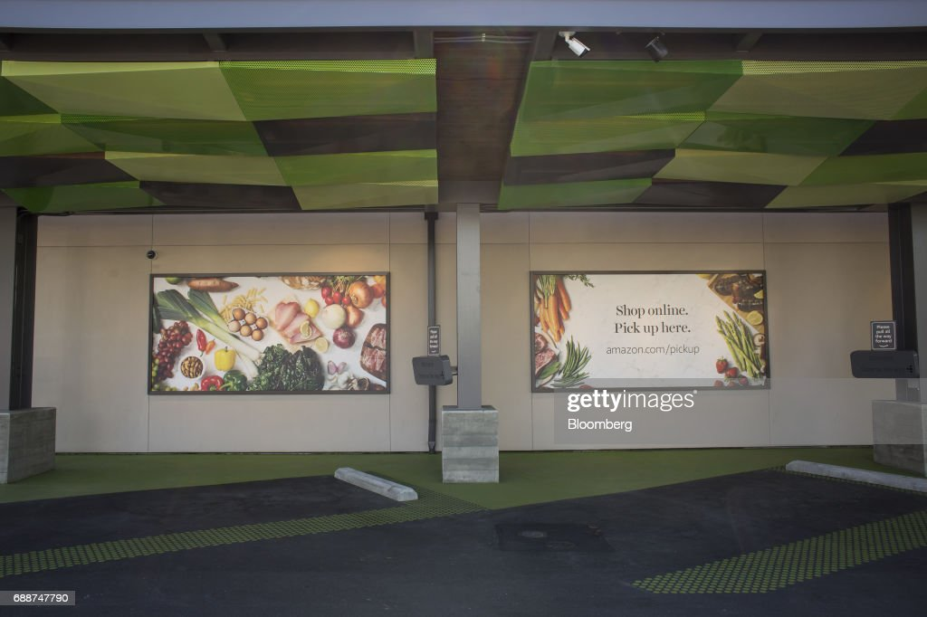 Advertisements are displayed above parking spots at an AmazonFresh Pickup location in Seattle, Washington, U.S., on Friday, May 26, 2017. Amazon.com Inc. opened two grocery pickup kiosks in Seattle, part of its latest effort to enter the $800 billion grocery market and compete with 'click and collect' shopping options from big box competitors like Wal-Mart Stores Inc.