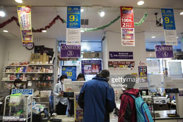 Advertisements for Ant Financial Services Group's Alipay an affiliate of Alibaba Group Holding Ltd hang above cashier counters at a Takeya Co Ueno...