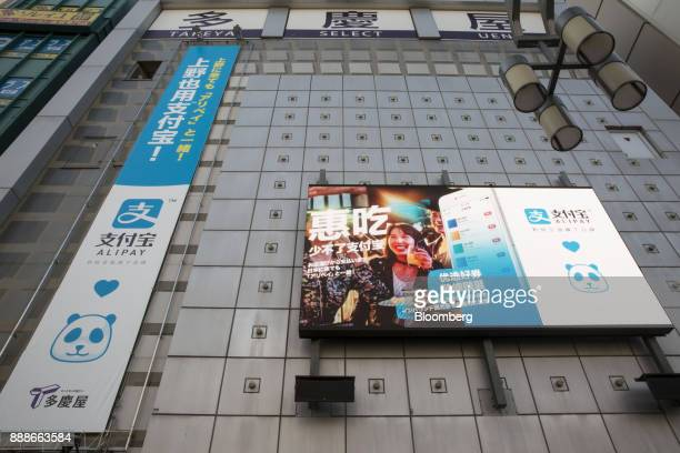 Advertisements for Ant Financial Services Group's Alipay an affiliate of Alibaba Group Holding Ltd are displayed outside a Takeya Co Ueno Select shop...