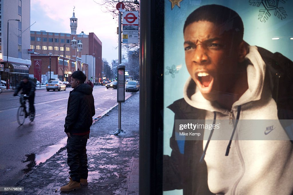 Advertising at a bus stop on Whitechapel High Street An Asian youth waits in the snow beside a poster which appears to be shouting a him Perhaps a...