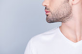 Advertising barbershop concept. Profile close up half face cropped portrait of handsome brunet  man with perfect stunning cut of his beard, in white t-shirt isolated on light grey background