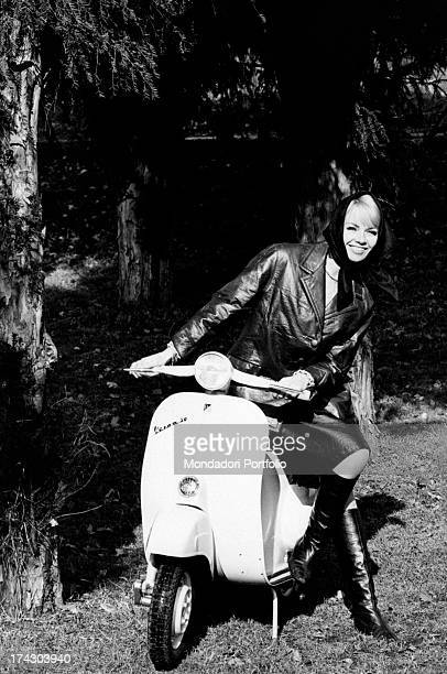 Advertisment of a model who resting on a Vespa Special shows a sports outfit suitable for going on a scooter the girl smiles at the camera and wears...