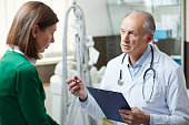 Aged doctor consulting his young patient and giving her recommendations