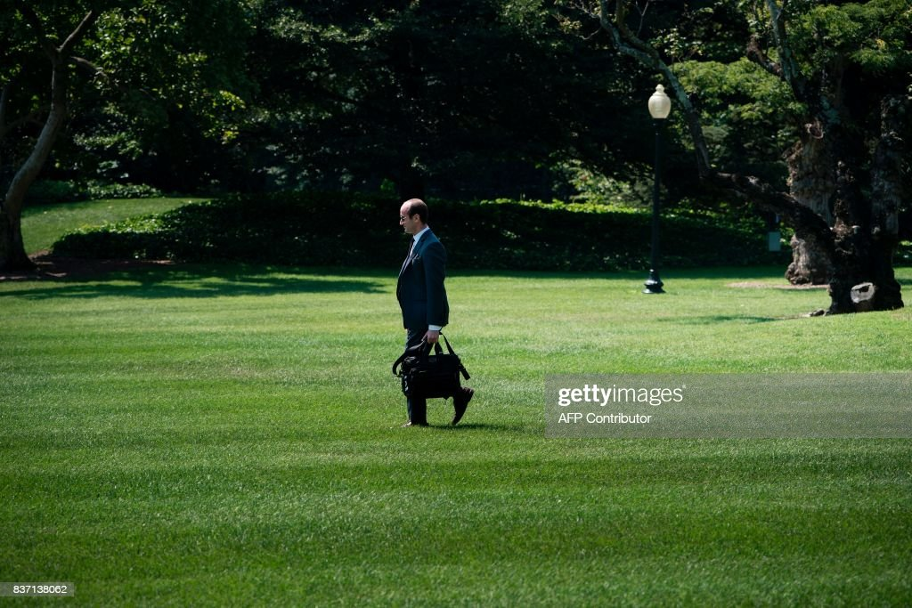 Advisor Stephen Miller follows as US President Donald Trump walks to Marine One on the South Lawn of the White House August 22, 2017 in Washington, DC. / AFP PHOTO / Brendan Smialowski