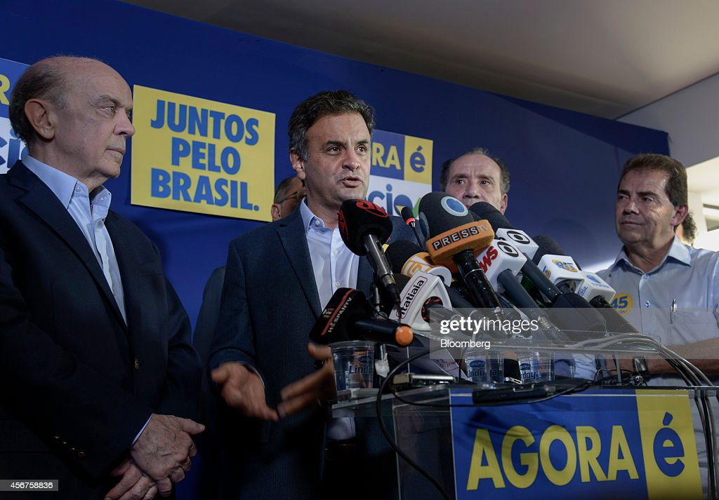 Aecio Neves, presidential candidate for the Brazilian Social Democracy Party, known as PSDB, center, speaks as senator Jose Serra, left, listens during a news conference in Sao Paulo, Brazil, on Monday, Oct. 6, 2014. Neves pulled off a surprise second-place finish to force a runoff with Brazilian President Dilma Rousseff, pitting a candidate favored by investors against an incumbent who says the end of her party's 12-year rule threatens policies that pulled 35 million out of poverty. Photographer: Paulo Fridman/Bloomberg via Getty Images