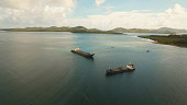 Aerial view Cargo and passenger ships in a beautiful lagoon on Siargao. Flying over the water surface of the sea with ships, blue sky and clouds.
