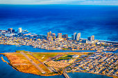 Aerial view of Atlantic City taken from an airplane. It is a beautiful sunny day with high clouds. The shot taken with a Canon 5D Mark iV shows bright blue Atlantic ocean and bay.