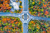 Aerial eagle eye view of a traffic circle roundabout located between beautiful autumn forest. The scene is located in Sofia, Bulgaria (Eastern Europe). The picture is taken with DJI Phantom 4 Pro dron