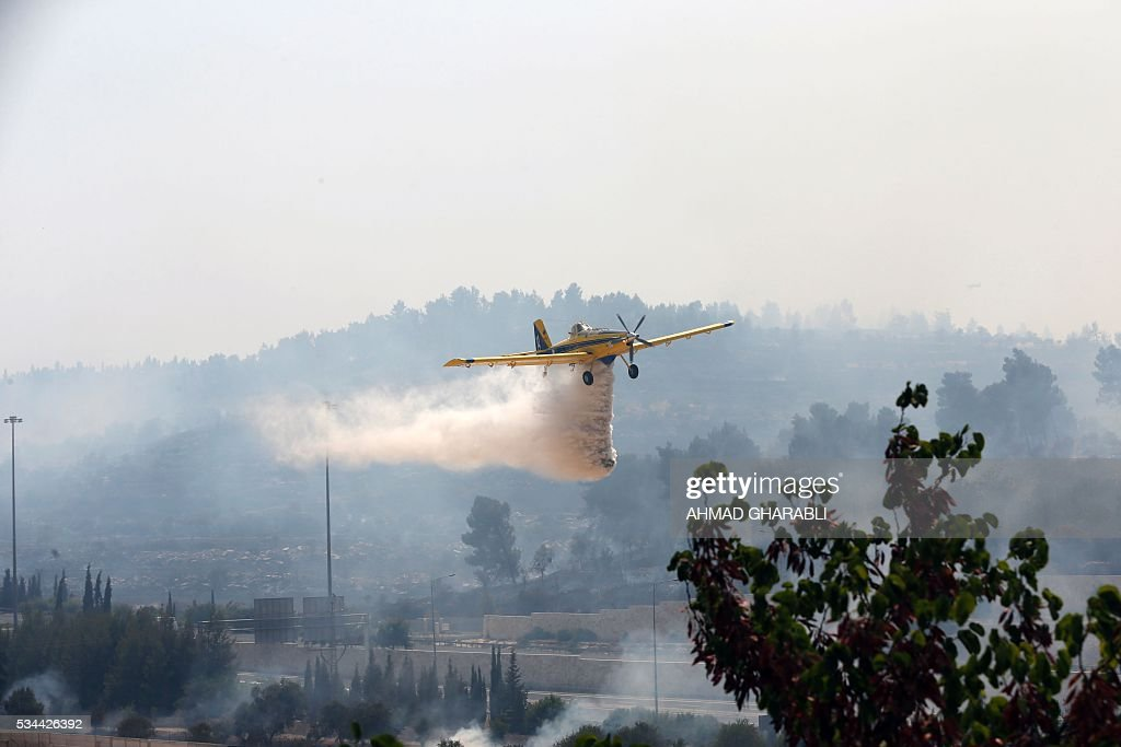 Aerial firefighters work to put out a fire that is spreading in the woods around Jerusalem on May 26, 2016 / AFP / AHMAD