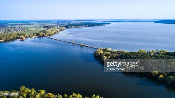 Aerial: Flying over a dam at spring land