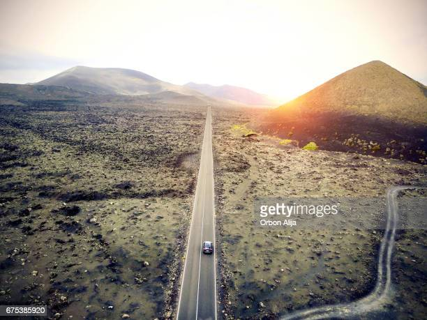 Aerial image of a car driving through a road in Lanzarote, Spain.