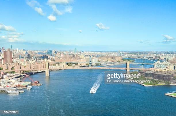 Aerial image of boat crossing underneath Brooklyn bridge, New York City, USA