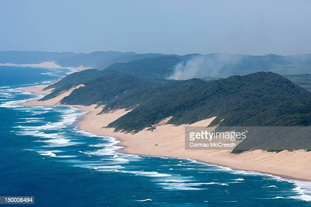 Aerial image of sea and sand dunes and coastal forest of Sodwana Bay, KwaZulu Natal, South Africa. Smoke rises from a fire in the coastal forest.