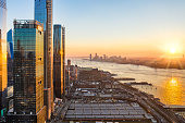 Aerial New York City waterfront skyline at sunset viewed from Hudson Yards towards Jersey City accross Hudson River.