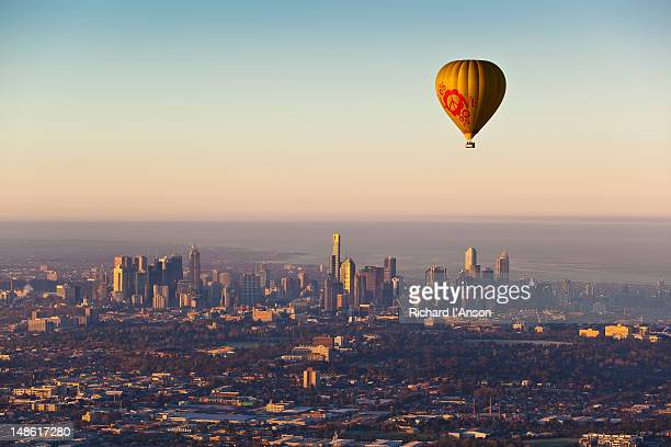 Aerial of hot air balloon flying over northern suburbs and city skyline.