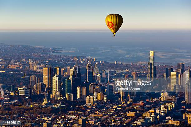 Aerial of hot air balloon flying toward city and Port Philip Bay.