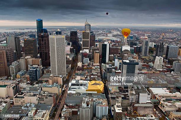 Aerial of hot air baloons flying over central business district.