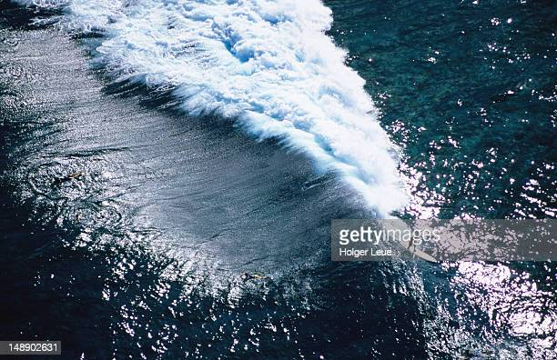 Aerial of surfer on giant wave.