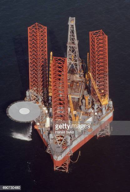 Aerial overview of an operational offshore cantilever or jack up oil rig platform showing the oil derrick and helicopter landing pad.