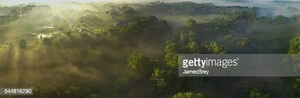 Aerial Panorama von neblig valley am Rande der Stadt, Sonnenaufgang