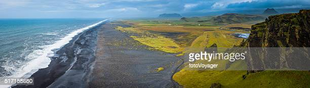 Aerial panorama over black beach wild Arctic Ocean surf Iceland