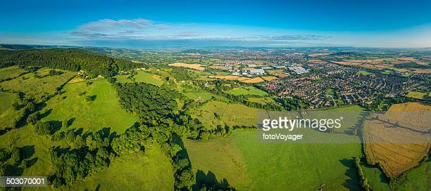 Aerial panorama over green countryside homes suburbs and town UK