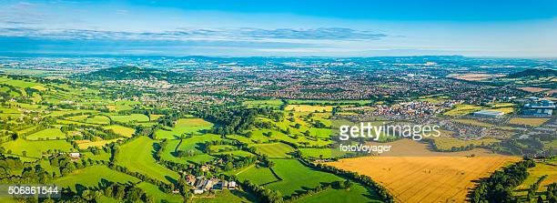Aerial panorama over green farmland pasture golden crops country town