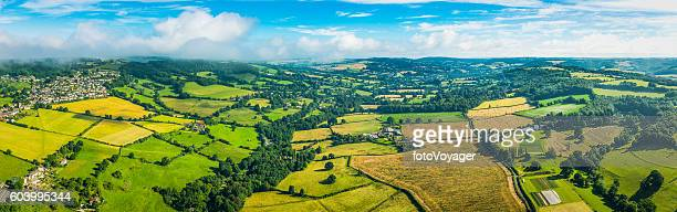Aerial panorama over green patchwork fields idyllic rural landscape Cotswolds