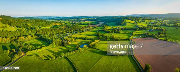 Aerial panorama over green summer fields rural farms picturesque pasture