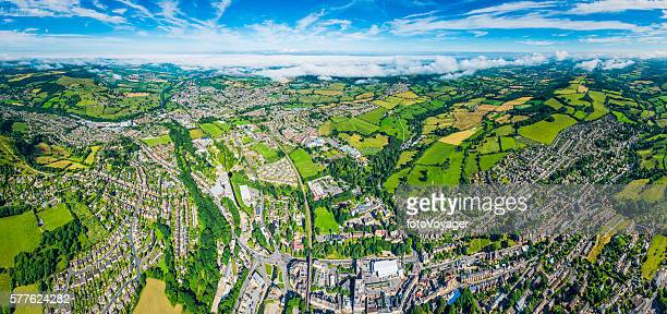 Aerial panorama over homes and gardens suburban streets green fields