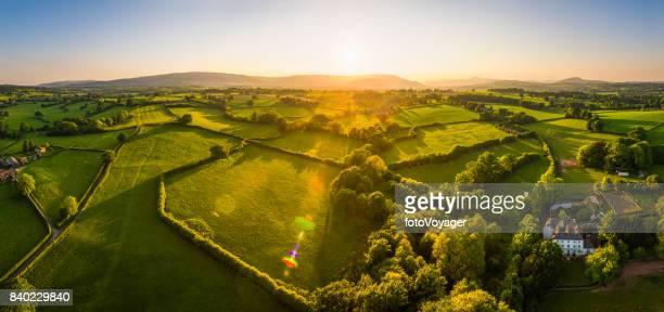 Panorama aérien au-dessus des fermes de campagne idyllique champs montagnes au coucher du soleil