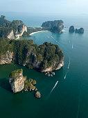 Photo from drone of Ao Nang beach, Krabi, Thailand. Boats float around the green rocks.