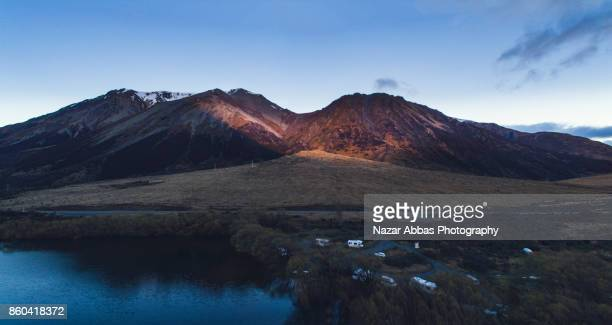 Aerial Panoramic view at Lake Pearson (Moana Rua) sun touching the peaks, High Country, South Island, New Zealand.