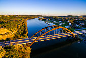 Aerial Pennybacker Bridge at Sunset Austin Texas Hill Country during a clear sky evening the sun sets behind the hills and casts a perfect golden hour glow on the Texas Hill country and the 360 Bridge