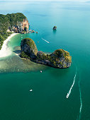 Aerial view of green rocky cliffs and boats on Phra Nang beach bay, Railay beach, in Krabi Province, coastline in Phuket, Thailand. James Bond Island.