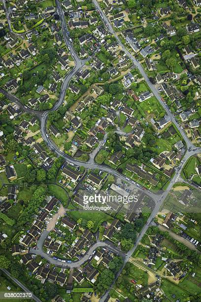 Aerial photo over suburban housing homes roads and green gardens