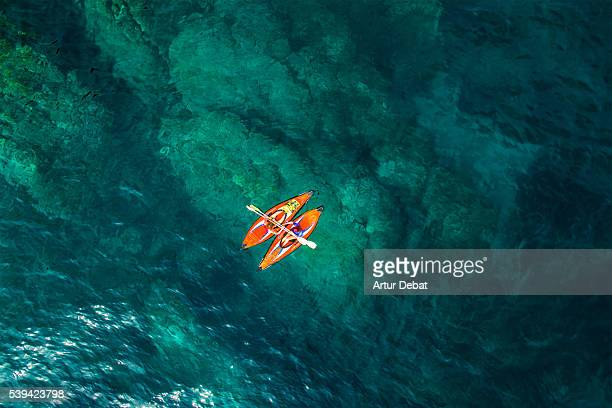 Aerial picture of two girls practicing kayak in a paradise place of the Costa Brava beach with beautiful and transparent blue water on summertime.