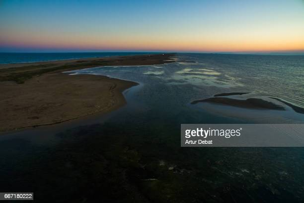 Aerial picture taken with drone flying over a beautiful narrow land between sea in both sides in the Ebro Delta nature reserve in sunset light during weekend travel in the zone in the Catalonia region.