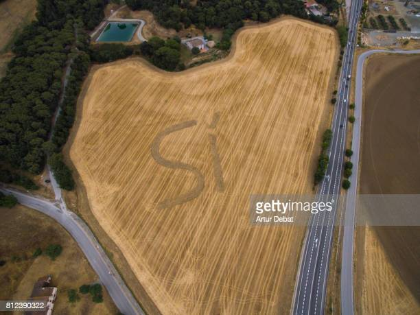 Aerial picture taken with drone flying over a huge SI (YES) marked in the agriculture field next to highway asking for vote yes in the independence referendum of Catalonia in the October of 2017.